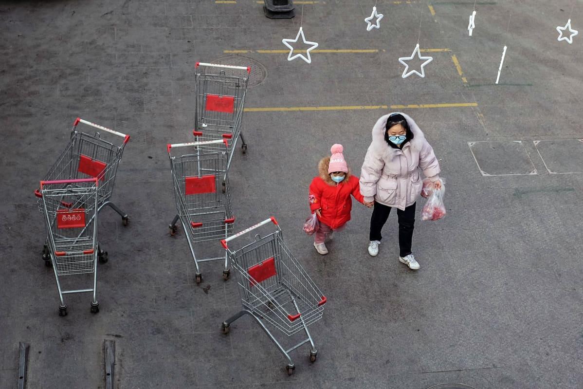 Nainen taluttaa lasta marketin ulkopuolella Pekingissä.