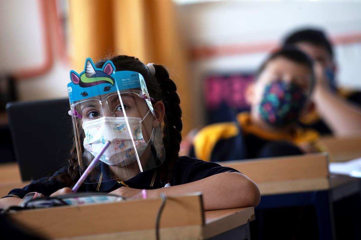 Suojamaskiin ja -vitriiniin pukeutunut lapsi luokkahuoneessa.