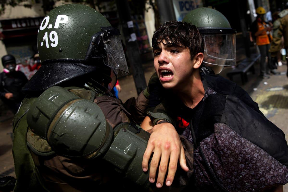 Mellakkavarusteisiin pukeutuneet poliisit pidättävät mielenosoittajan kadulla.