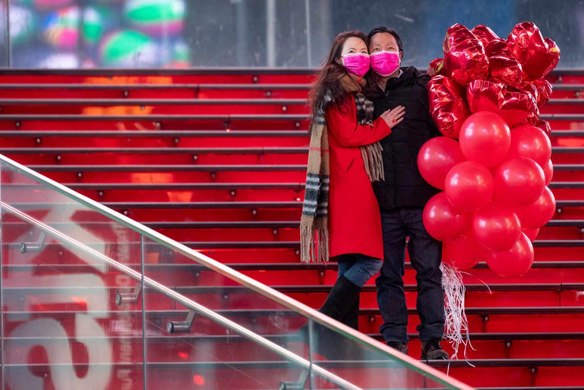 Pariskunta pitää kädessään ilmapalloja Times Squarella, New Yorkissa.