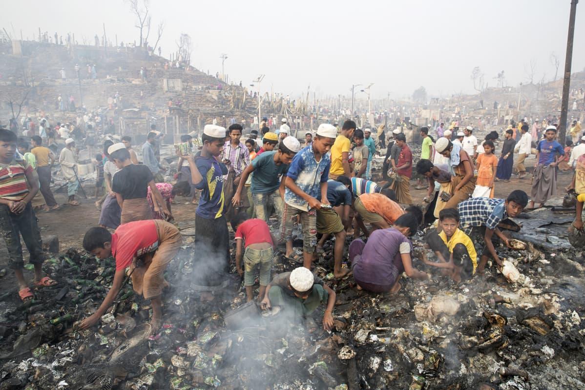 Pakolaiset etsivät omaisuuttaan tulipalon tuhon jälkeen.