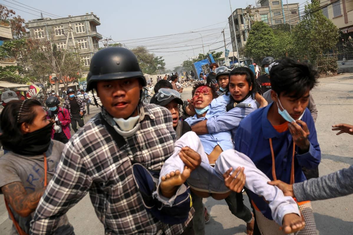 Mielenosoittajat kantavat haavoittunutta henkilöä pois mielenosoituksesta.