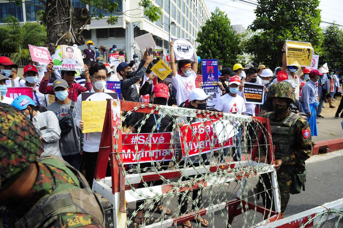Mielenosoittajat seuraavat kun Myanmarin armeijan sotilaat rakentavat piikkilankaestettä.