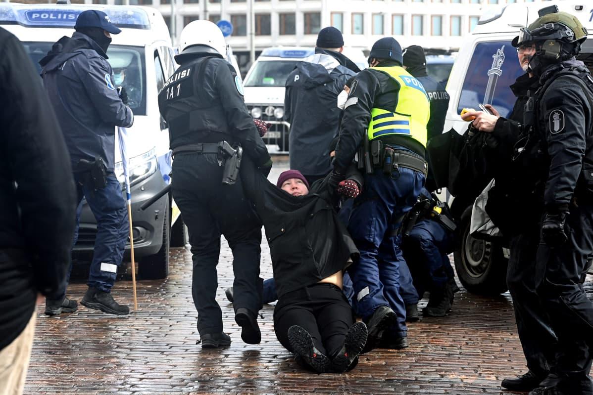 Poliisit raahaavat mielenosoittajaa Kauppatorilla.