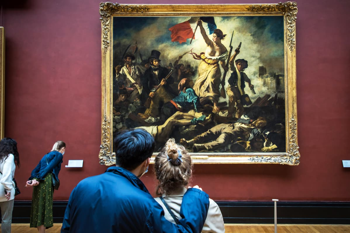 Museovieraat katselevat vallankumousta esittävää maalausta Louvressa.