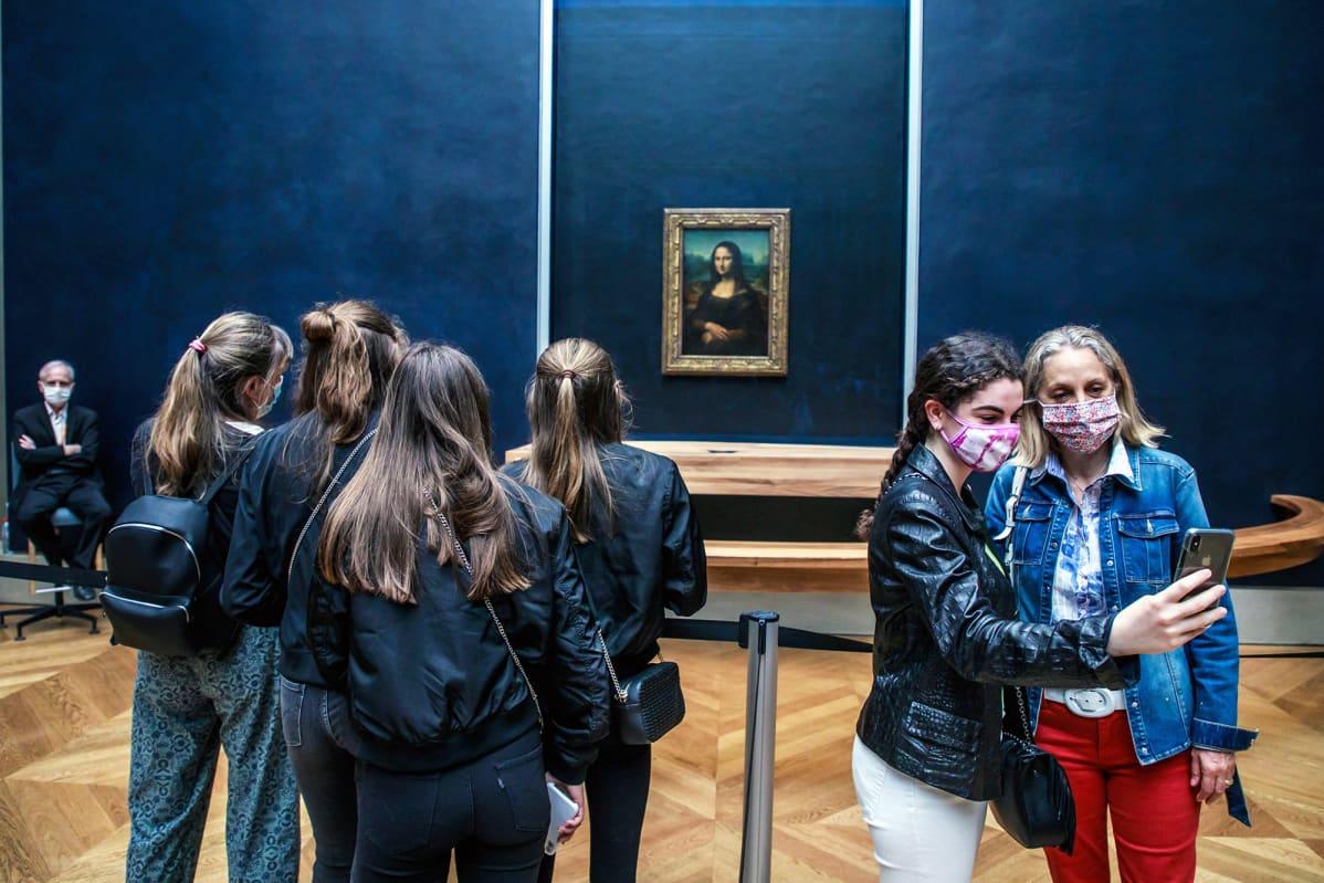 Museovieraa valokuvaavat itseään naista esittävän öljymaalauksen edessä Louvressa.