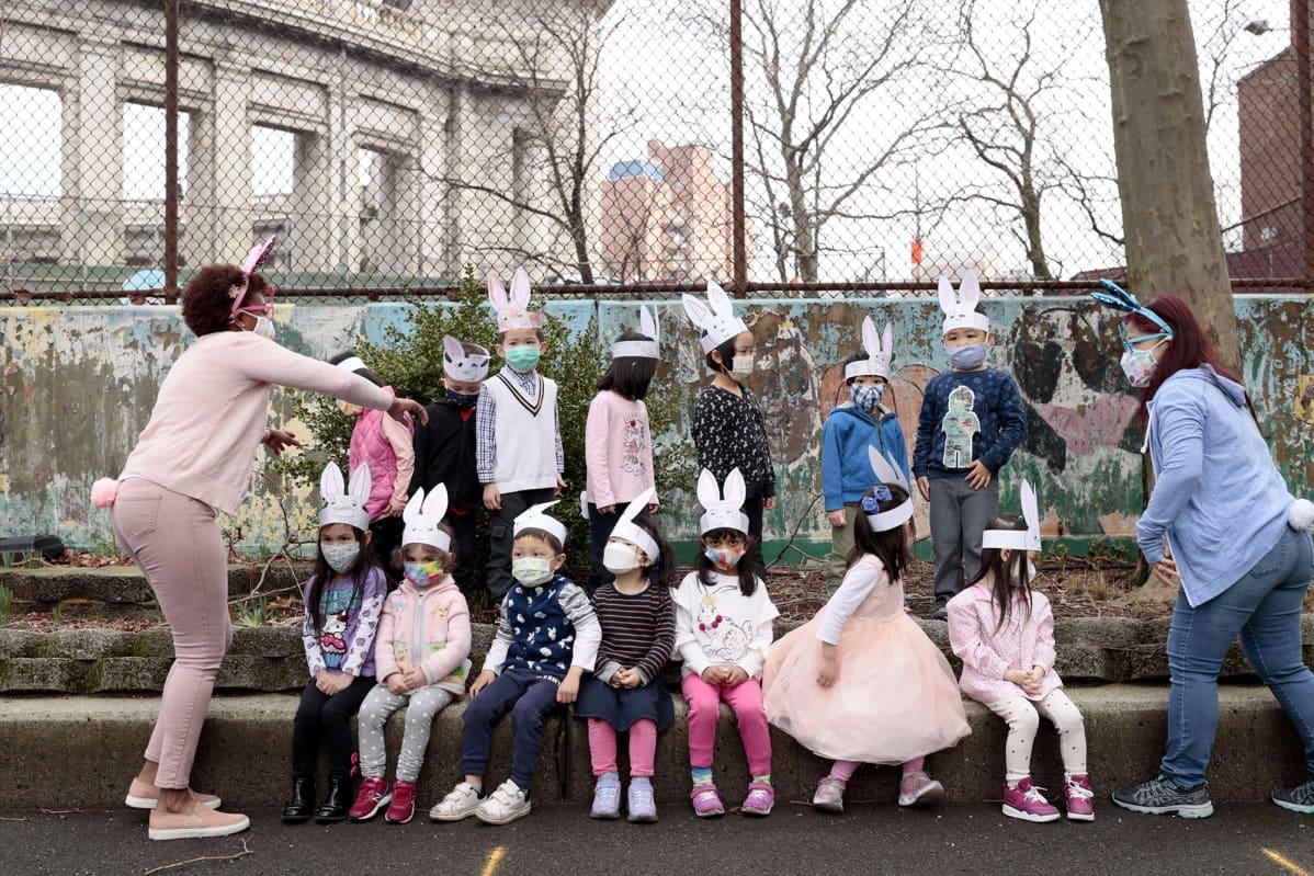 Kasvomaskeihin ja pupukorviin pukeutuneet koululaiset järjestäytyvät luokkakuvaan koulun pihalla.