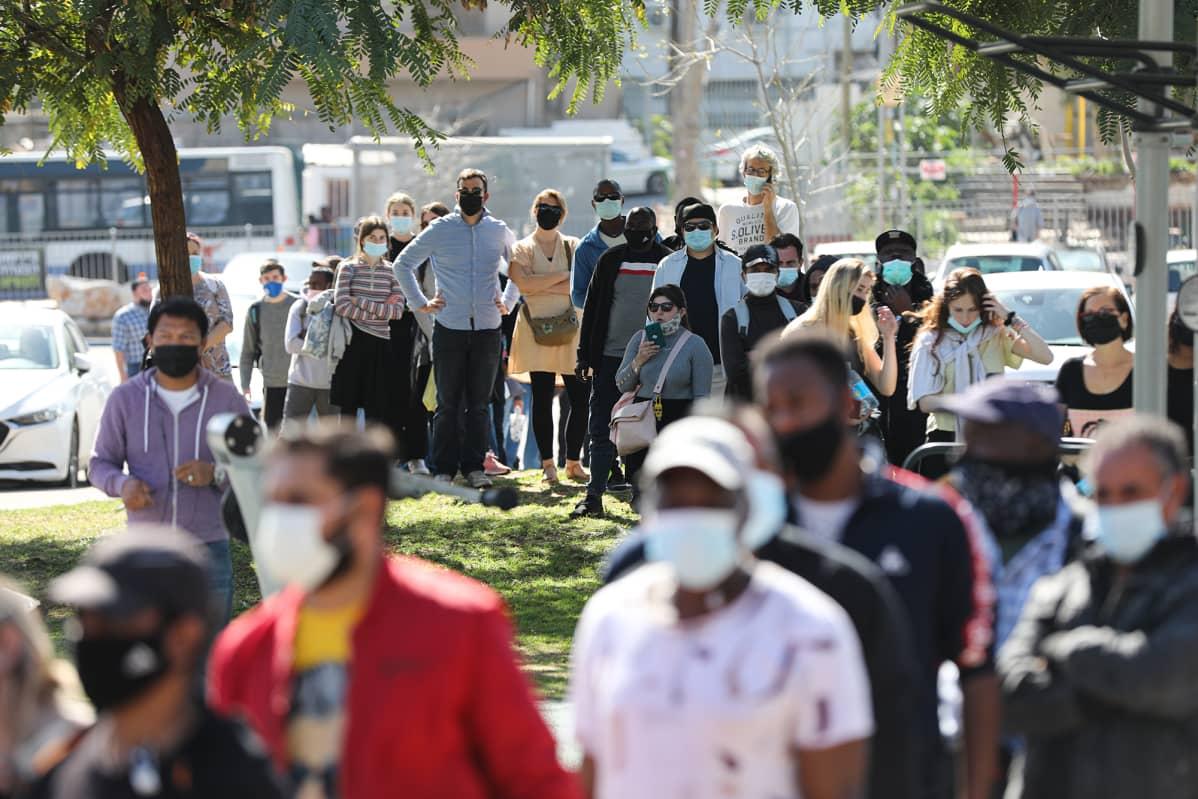 Ulkomaalaiset asukkaat Tel Avivissa jonottavat koronarokotukseen.