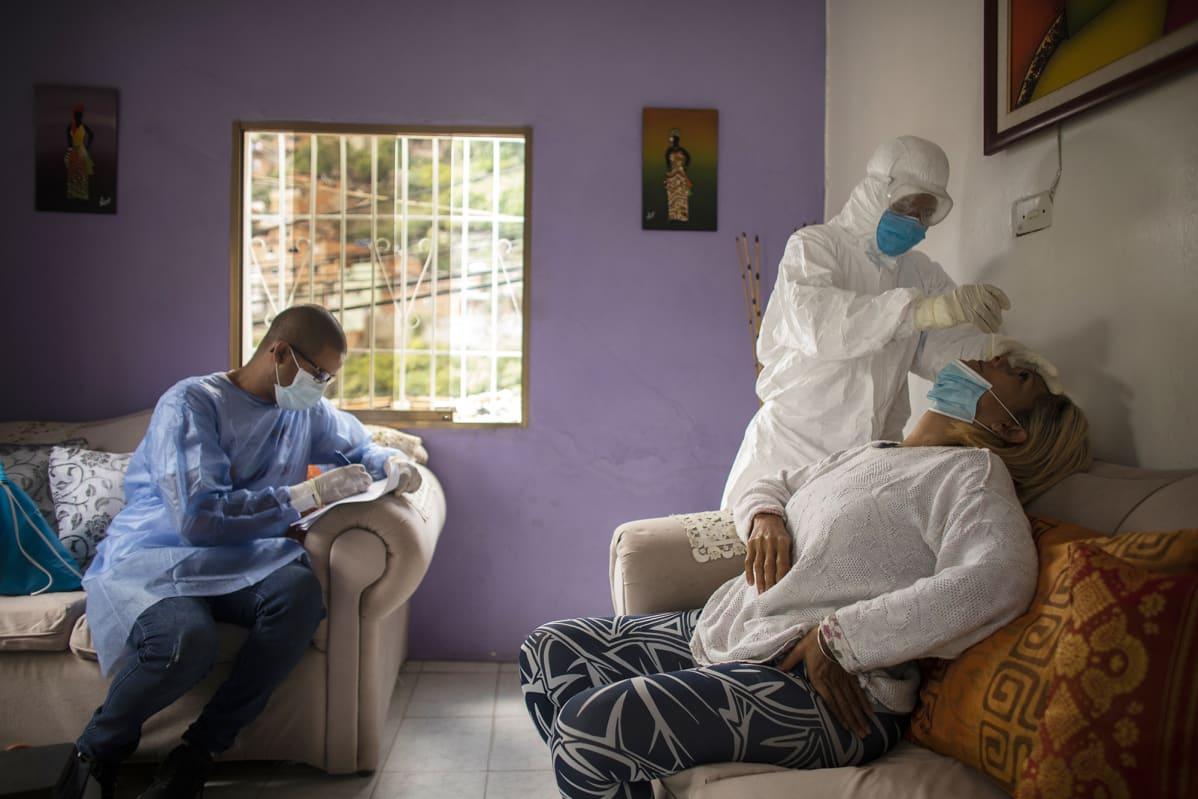 Sairaanhoitaja ottaa naiselta koronavirustestiä.