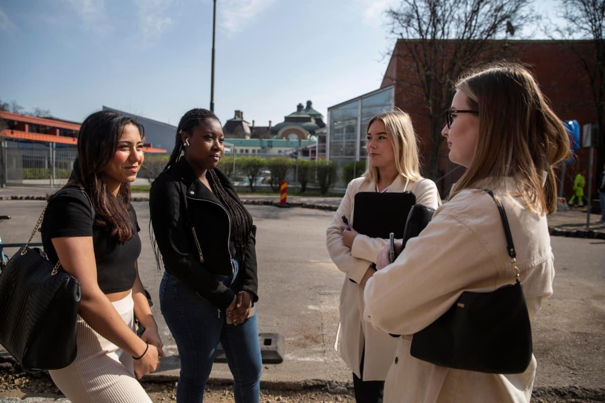 Nejä nuorta naista keskustelee toistensa kanssa koulun ulkopuolella.