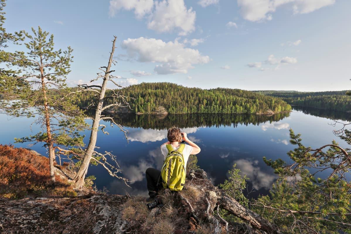retkeilijä katsoo järvimaisemaa korkealta kalliolta