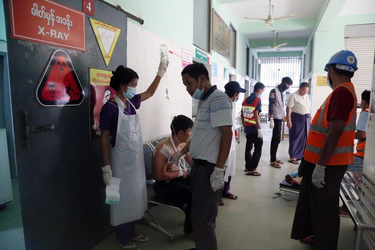 Loukkaantuneet ihmiset odottavat hoitoon pääsyä sairaalan käytävällä.