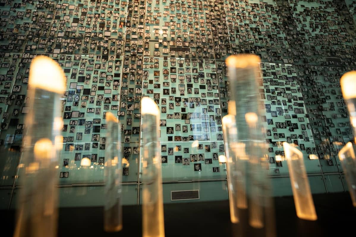 Muistomerkki, jossa paljon valokuvia seinällä.