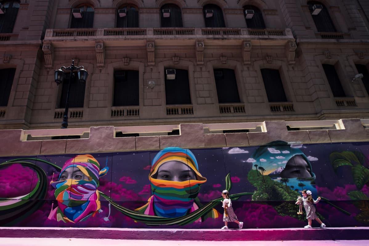 Kaksi lasta ohittaa seinämaalauksen, jossa on naisten kasvoja.