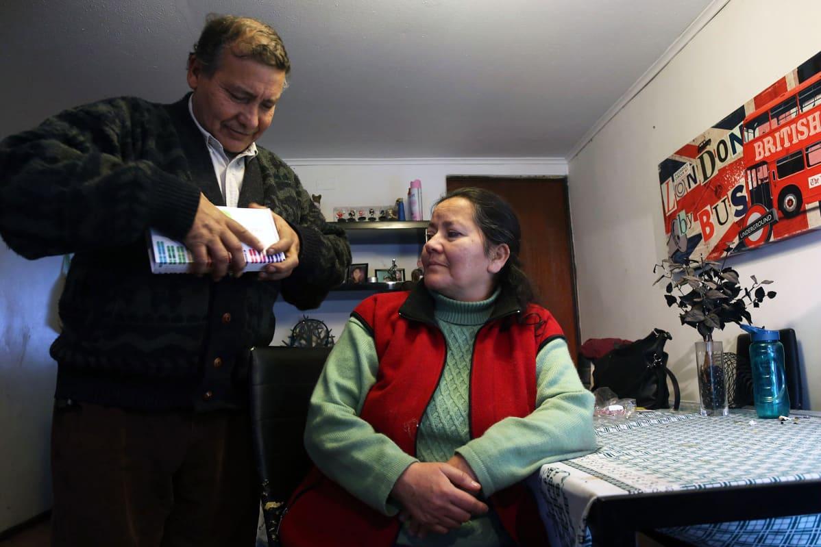 Chileläinen pariskunta avaa DNA-testipakkauksen.