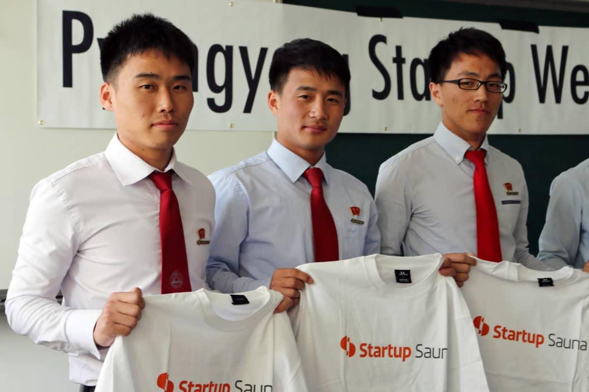 Startup Sauna Pohjois-Koreassa. Opiskelijat ovat pukeutuneet vaaleisiin kauluspaitoihin ja punaisiin kravatteihin. Kaikilla heistä on samantyyppiset lyhyet hiukset.