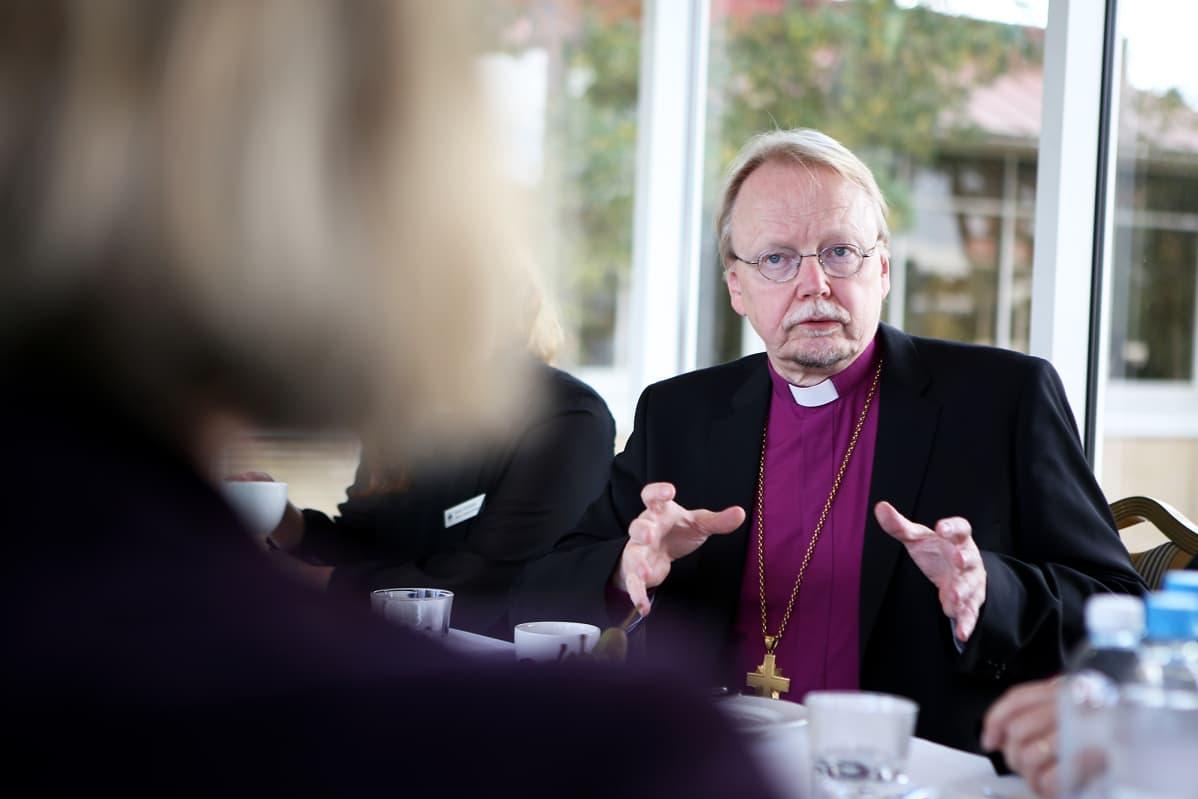 Arkkipiispa Kari Mäkinen istuu keskustelee pöydässä.
