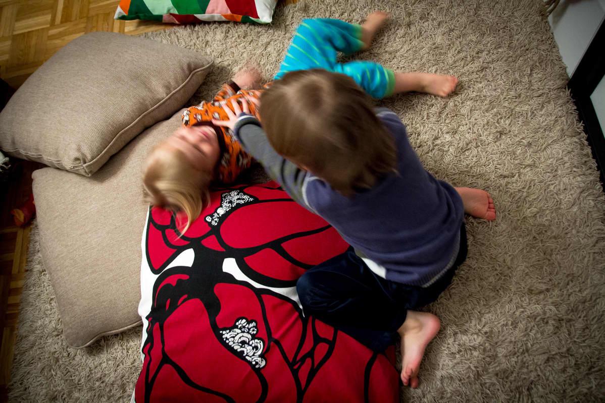 Veljekset painimassa lattialla kotonaan
