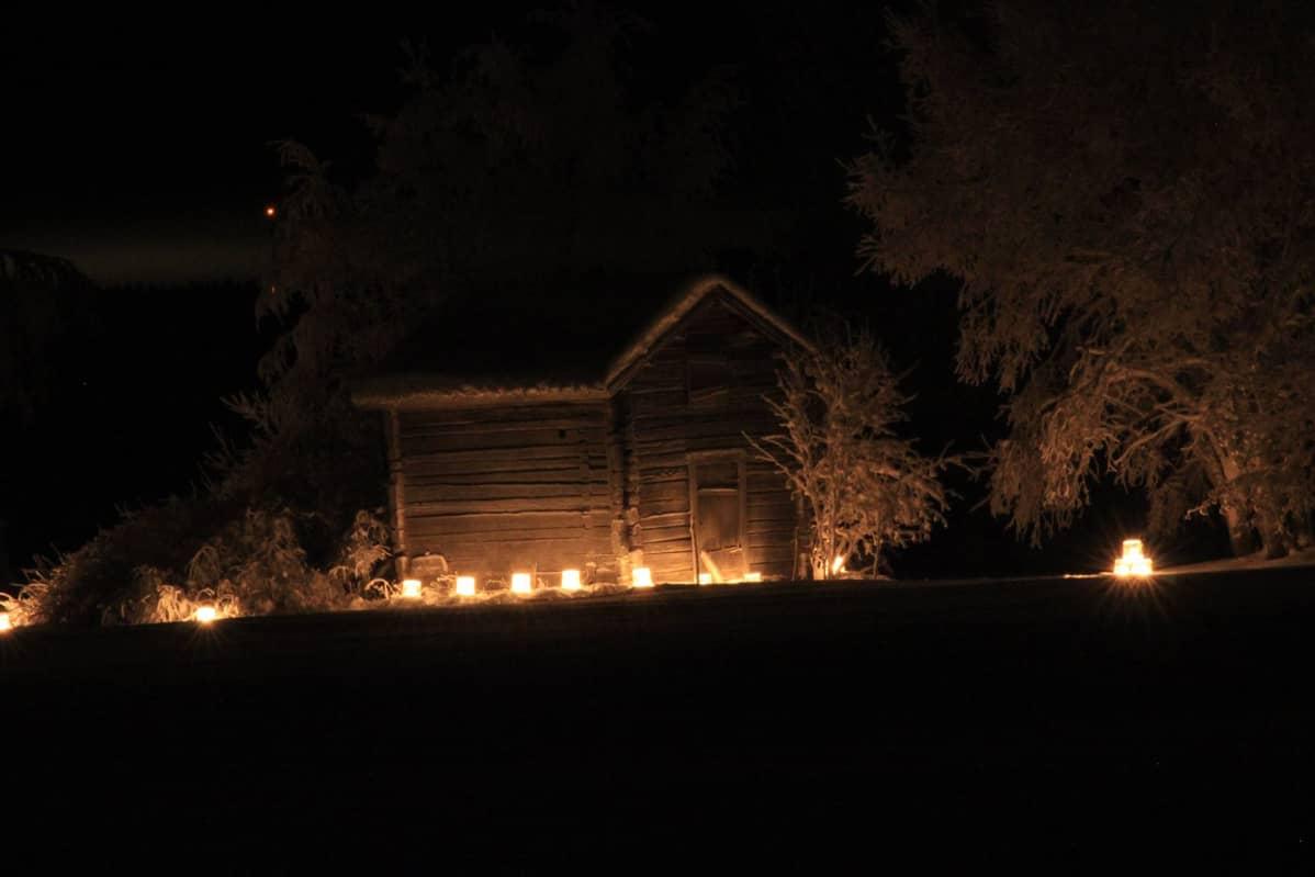 Jäälyhtyjä vanhan hirsiladon edessä pimeällä