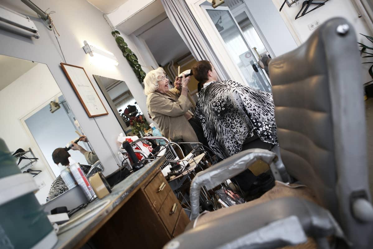 95-vuotias Aira Ehrlund leikkaa miehen hiuksia koneella.