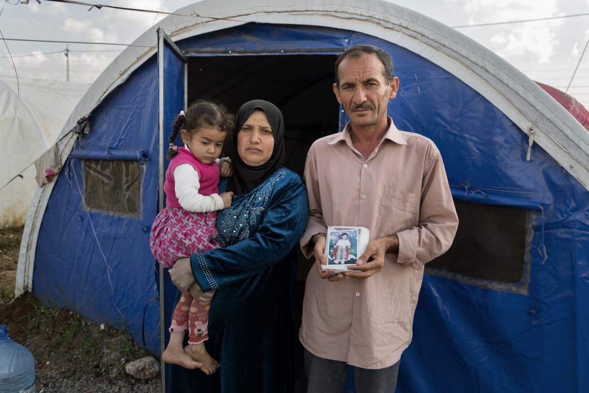 Pariskunta ja lapsi teltan edessä.
