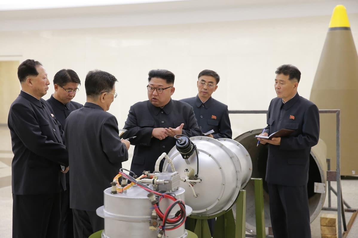 Kuusi tummahiuksista miestä puvat päällä suuren metallikoteln ympärillä.