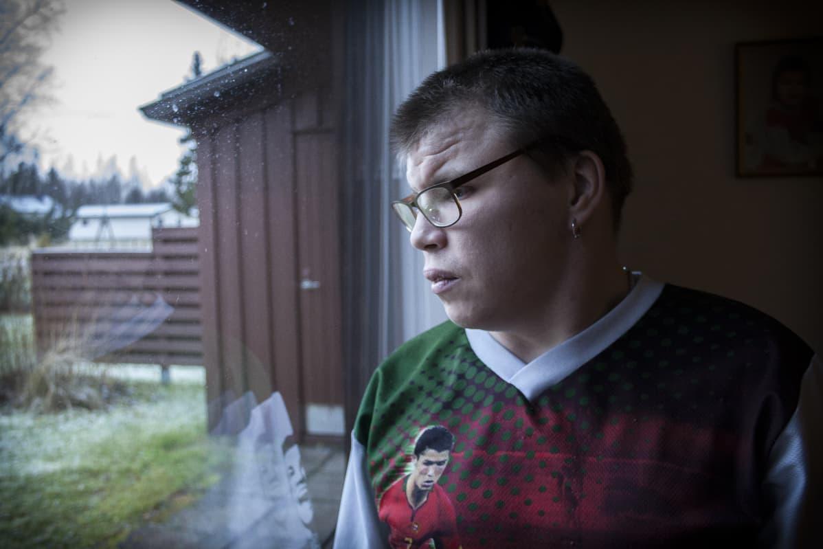 Kari-Matti Viitala katselee olohuoneen ikkunasta ulos.