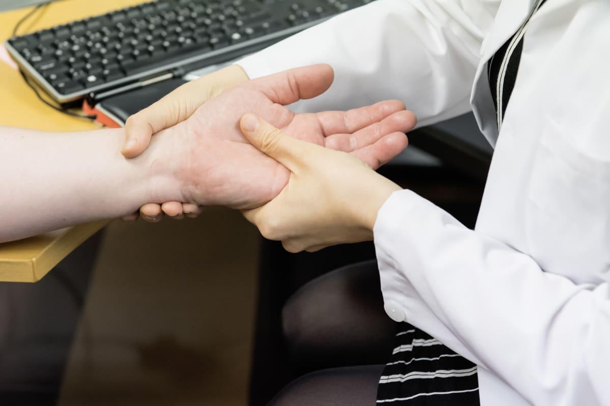 Lääkäri tunnustelle potilaan kättä.