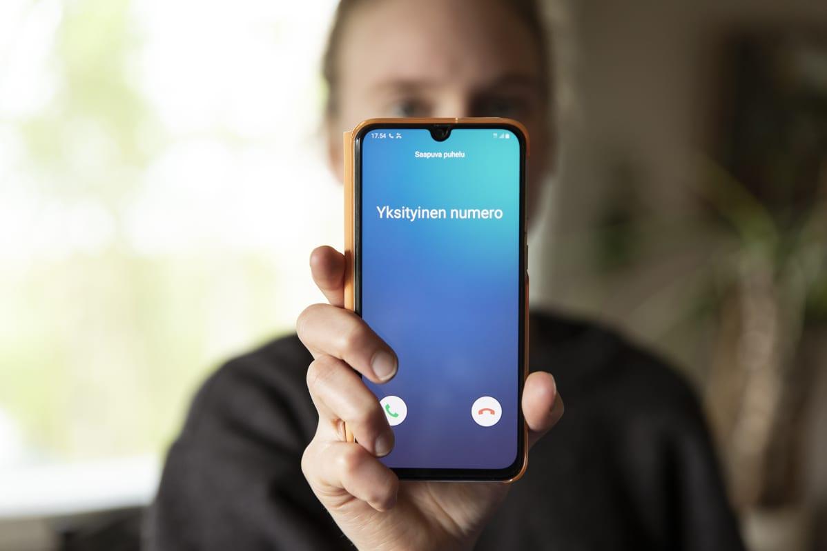 Henkilö pitelee puhelinta, jossa lukee yksityinen numero.