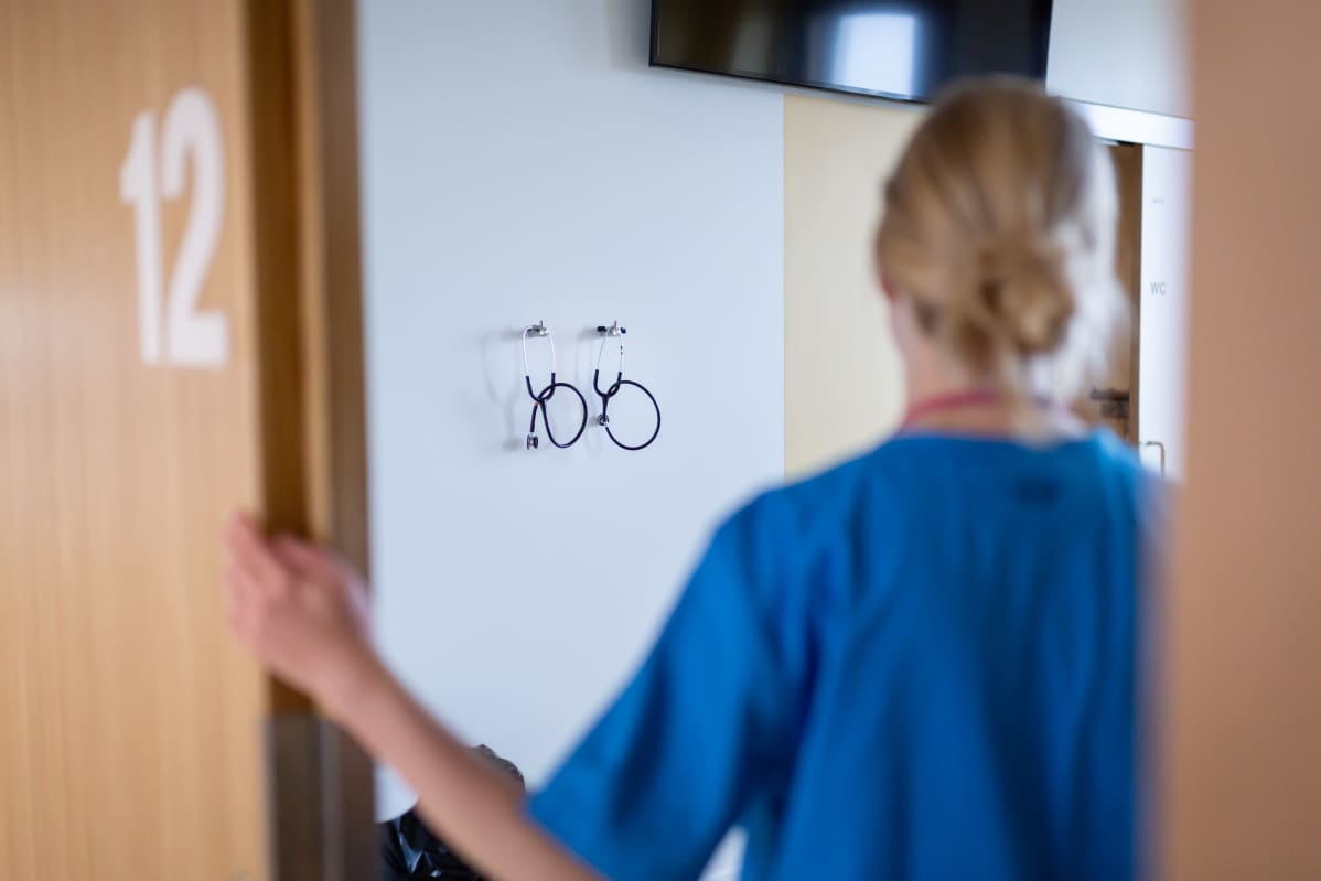 Sairaanhoitaja kuvattuna takaa potilashuoneen ovella. Taustalla stetoskooppeja.