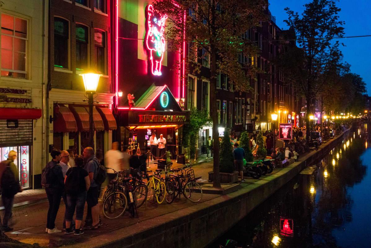 Red light district på natten. I bildens högermiljö ser man en av Amsterdams kanaler.