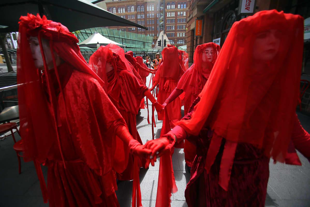 Punaisiin asuihin pukeutuneita ilmastomielenosoittajia Australian Sydneyssä.