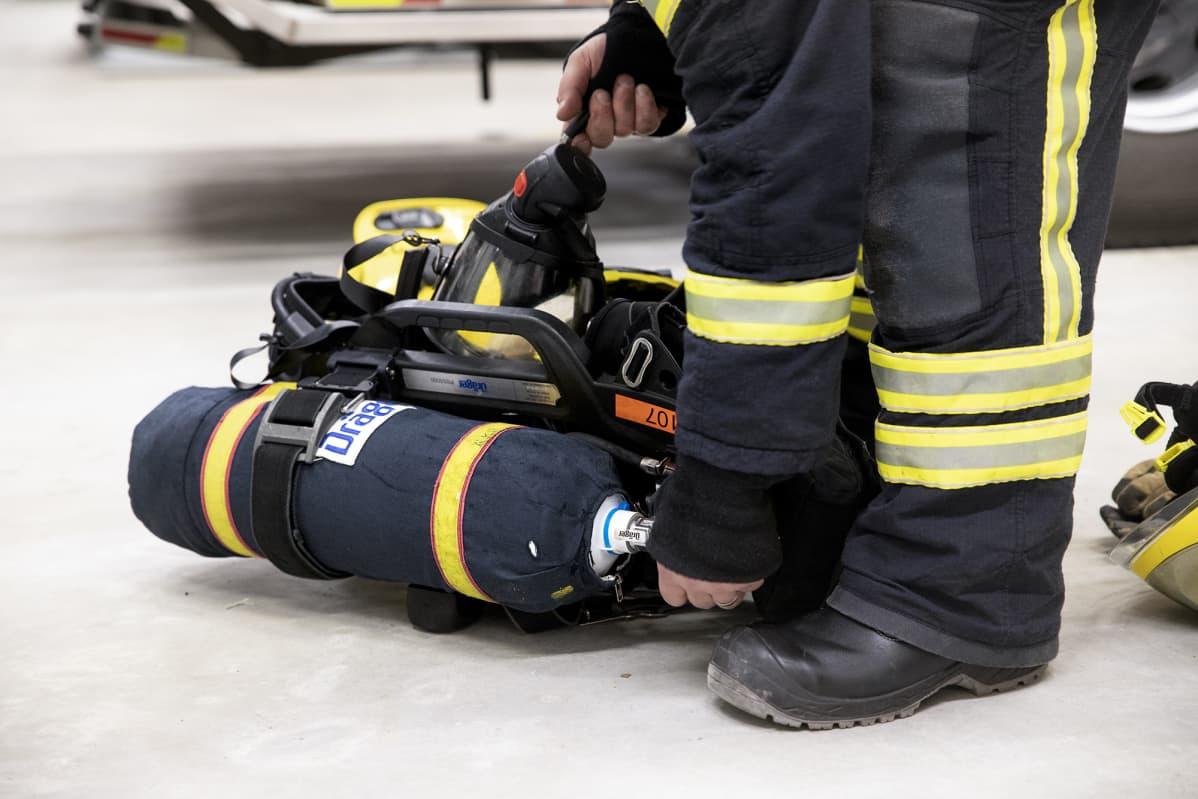Palomiehen kädet säätävät savusukelluksessa käytettävää paineilmapulloa.