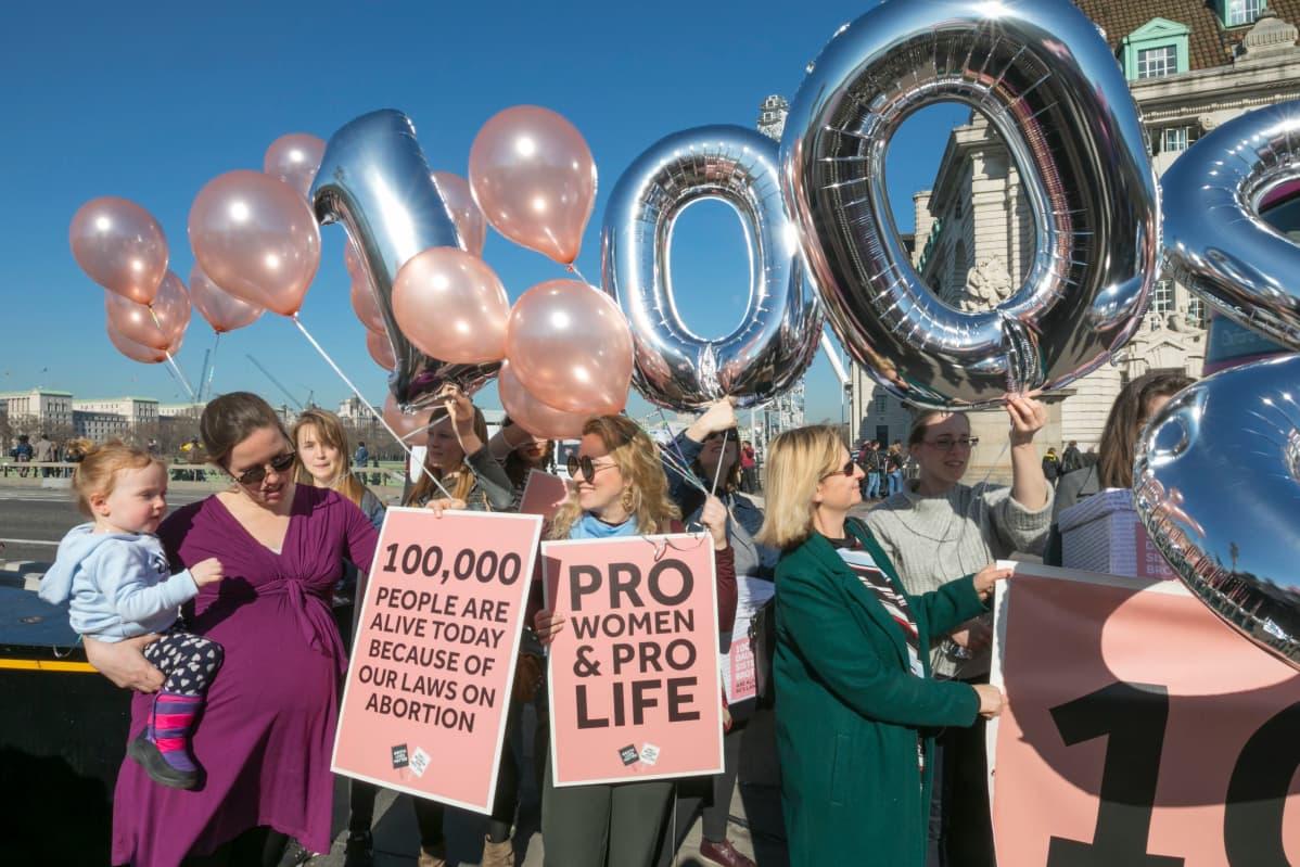 Aborttia vastustavat naiset kantavat kylttejä ja ilmapalloja Pohjois-Irlannin toimiston edustalla helmikuussa 2019. Kyltissä lukee: sata tuhatta ihmistä on elossa aborttilakiemme ansiosta.