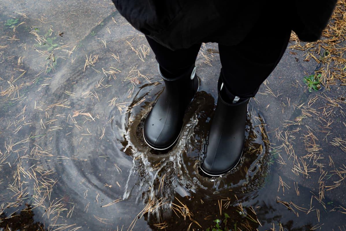 Nainen saappaat jalassa vesilätäkössä.