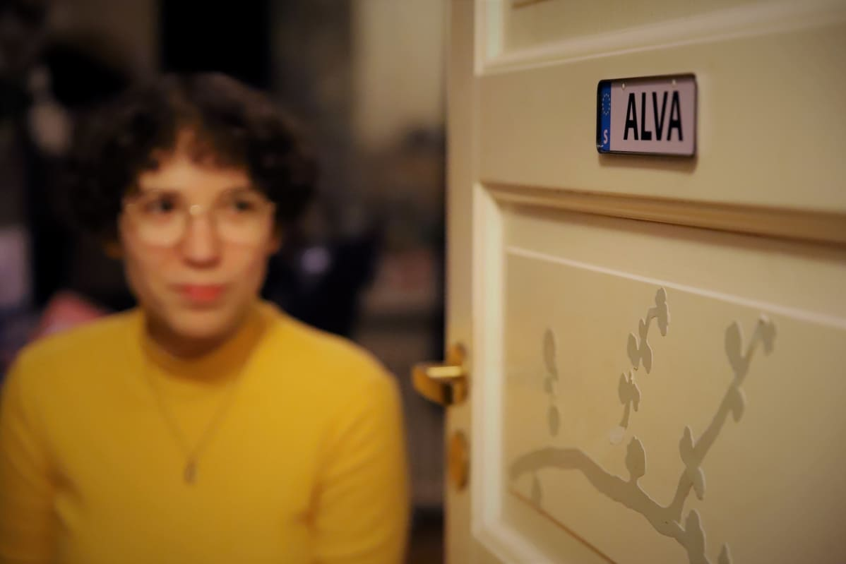 Alva Fontell katsoo huoneensa ovessa olevaan Alva-kylttiä.