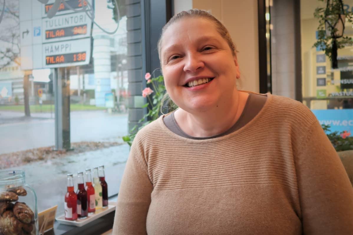 Sari Koskinen hymyilee kahvilan pöydässä