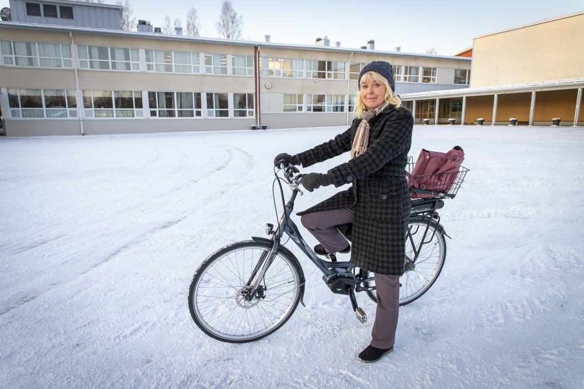 Marita Misukka-Kyyrö polkupyörän kanssa koulun edessä.