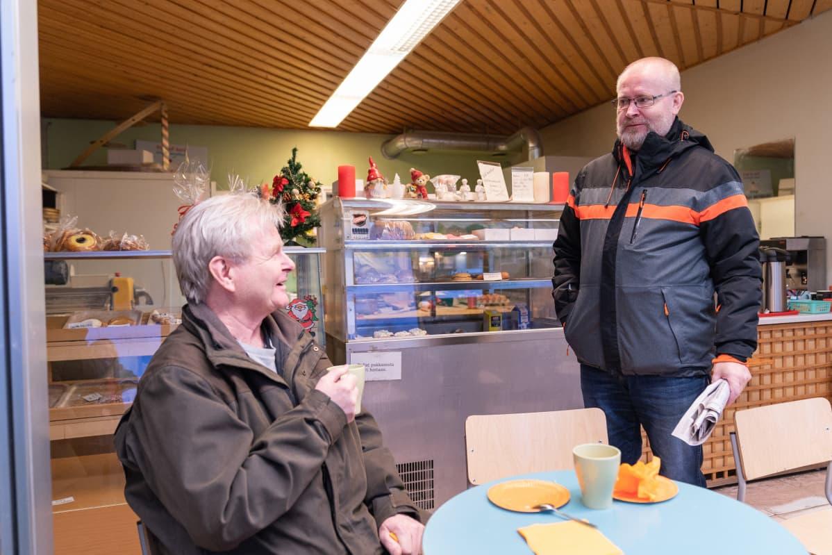 Jari Lindström keskustelee kahvilassa Aki Haimin kanssa
