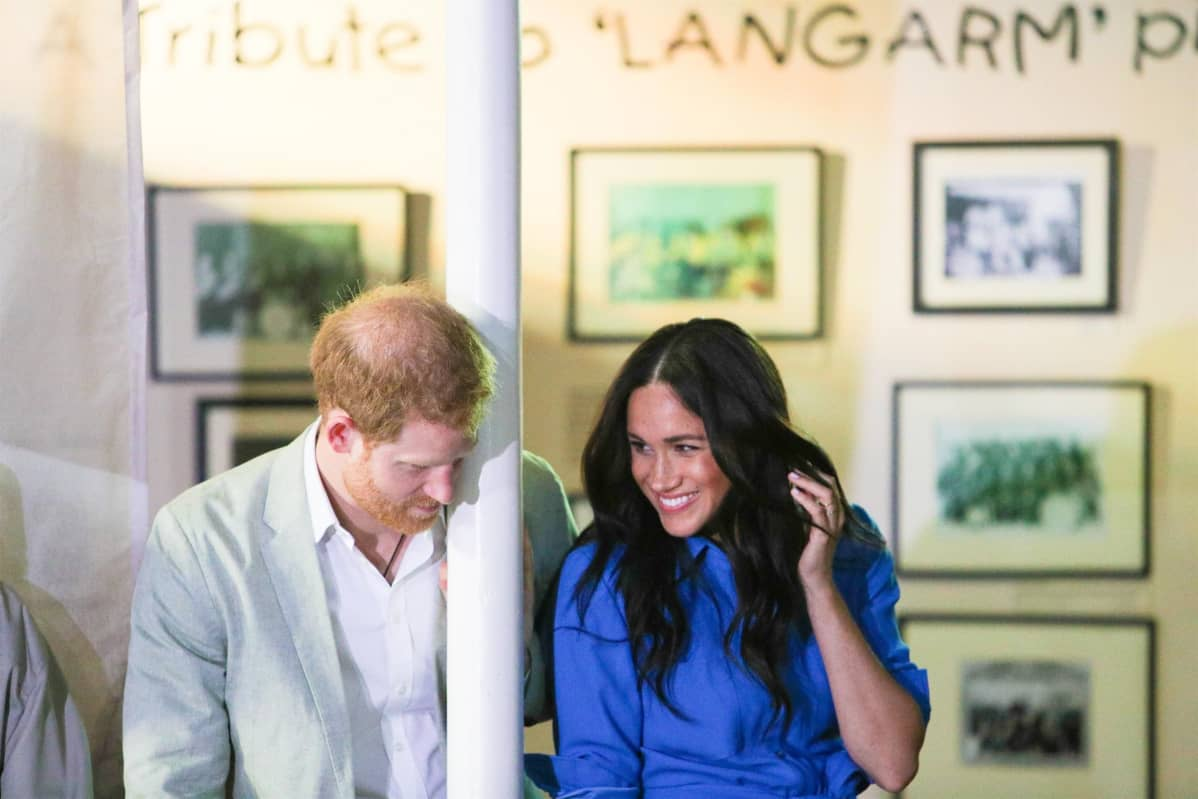 Pylvääseen nojaava prinssi Harry ja hymyilevä Meghan.