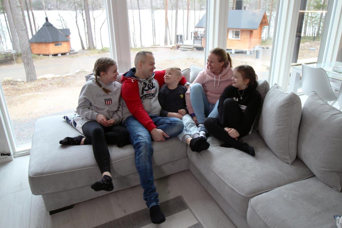 Hahlien perhe istumassa sohvalla.