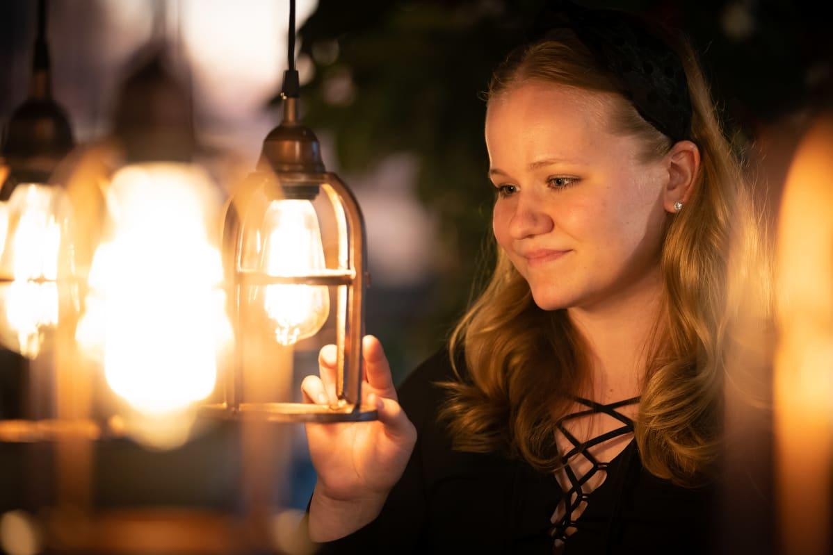 Amanda Laakkonen sisustuslamppujen keskellä.
