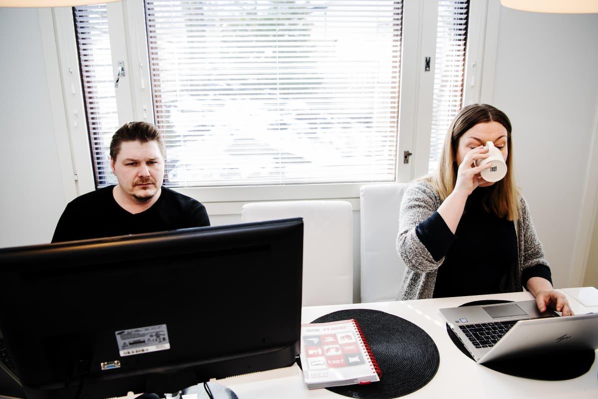Sami Sjöblom ja Tiina Toivonen etätyöskentelevät keittiön pöydän ääressä.