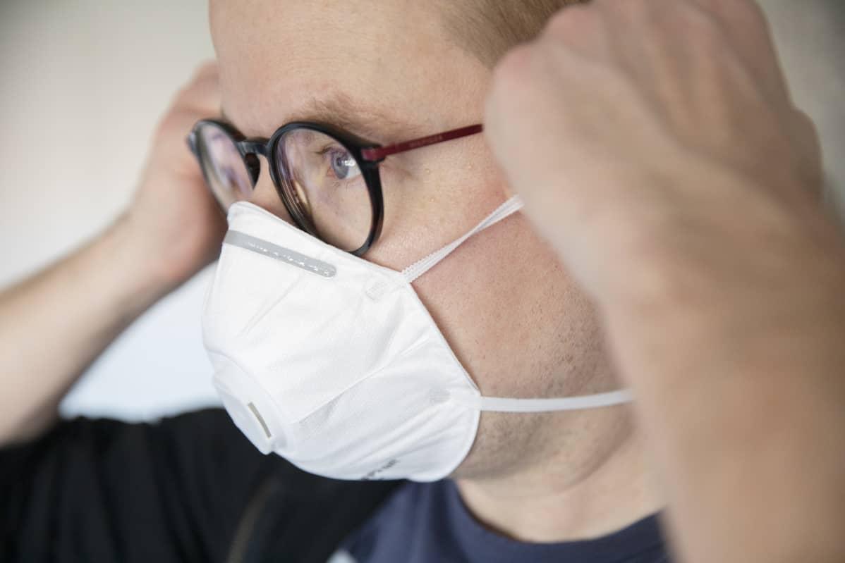 mies asettaa itselleen hengityssuojainta