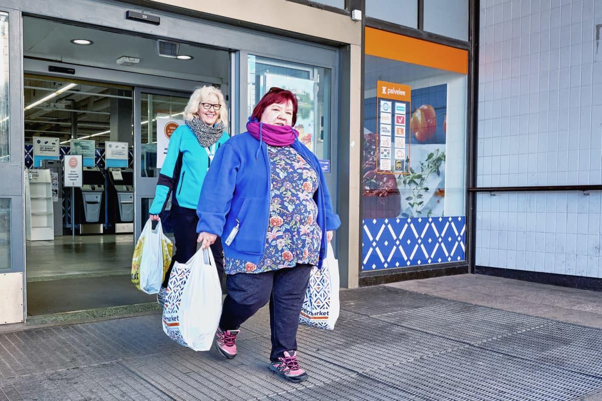 Tiina Marin ja Jaana Riihelä Kotkan opetustoimesta ovat olleet mukana yli 70-vuotiaiden asiointipalvelussa. Kuvassa he tulevat ostoskassien kanssa ulos ruokakaupasta.