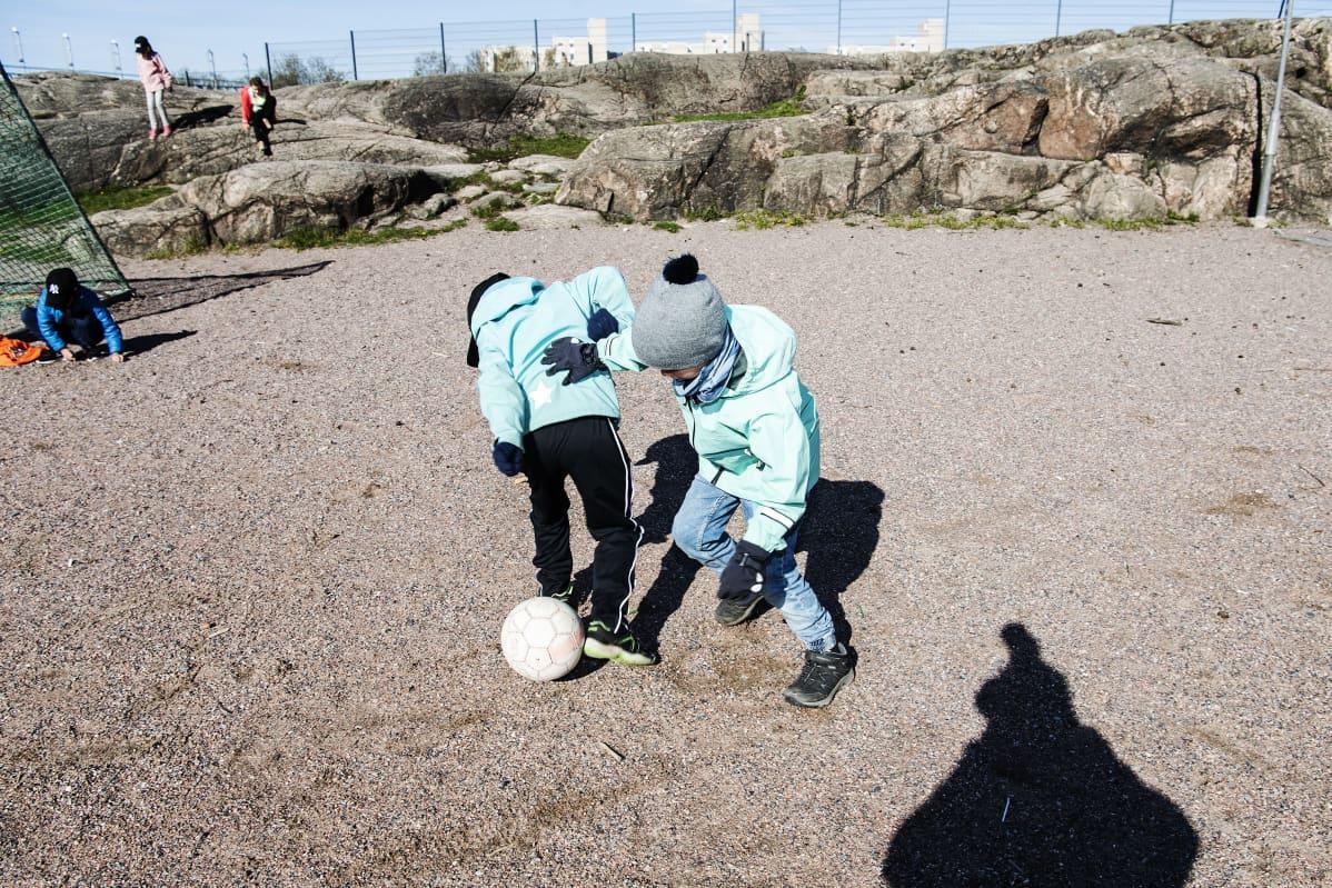 Kuvassa Ossian Eskelinen pelaa jalkapalloa koulun pihalla.