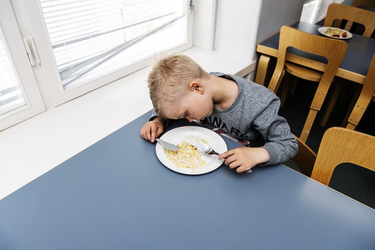 Kuvassa Ossian Eskelinen tarkastelee kouluruoka-annostaan.