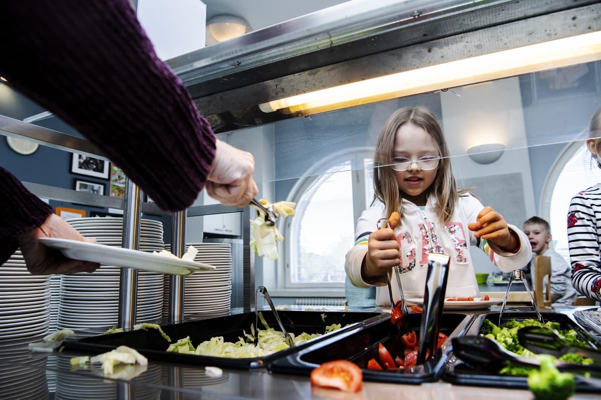 Kuvassa Selma Pihlaja ottaa ruokaa.
