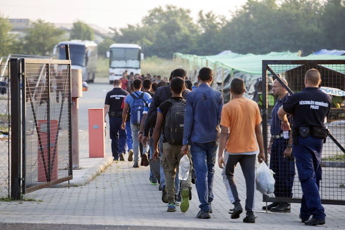 Siirtolaisia kävelee aidan taakse leiriin poliisin saattamina.