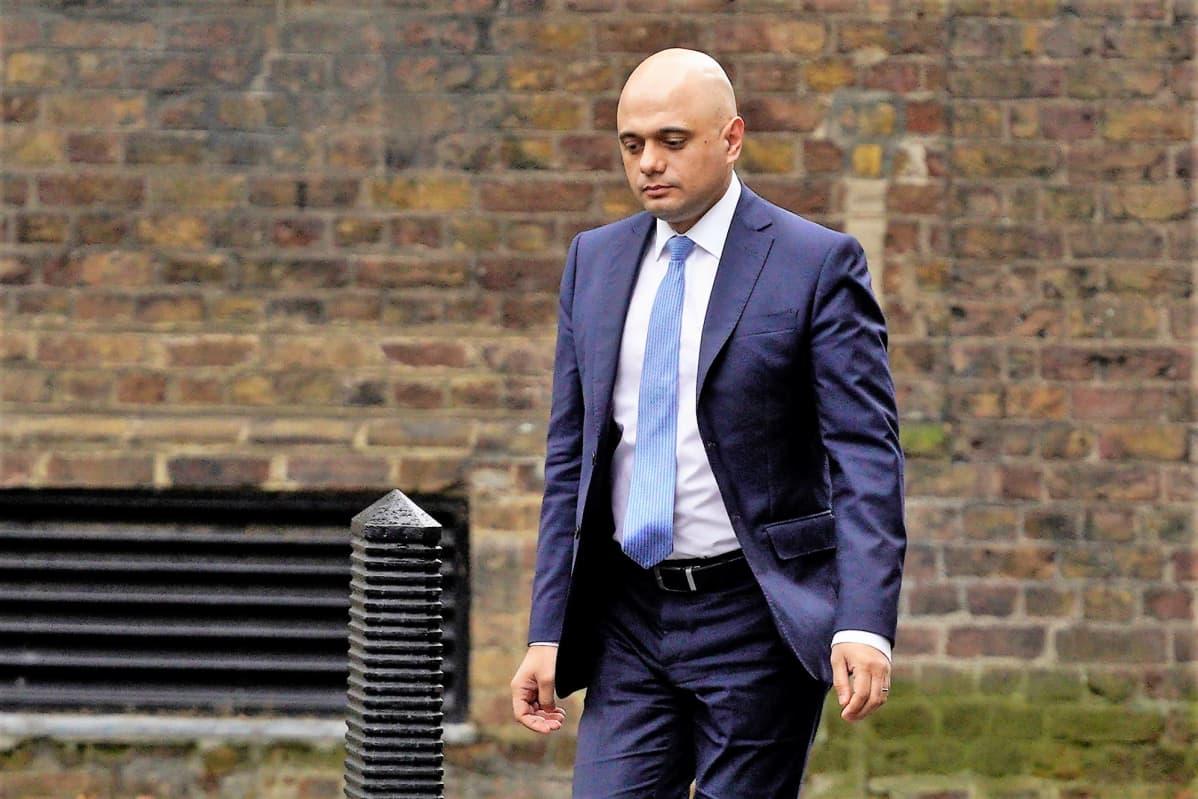 Sajid Javid kävelee tiiliseinän edustalla. Hänellä on sininen puku ja vaaleansininen kravatti.